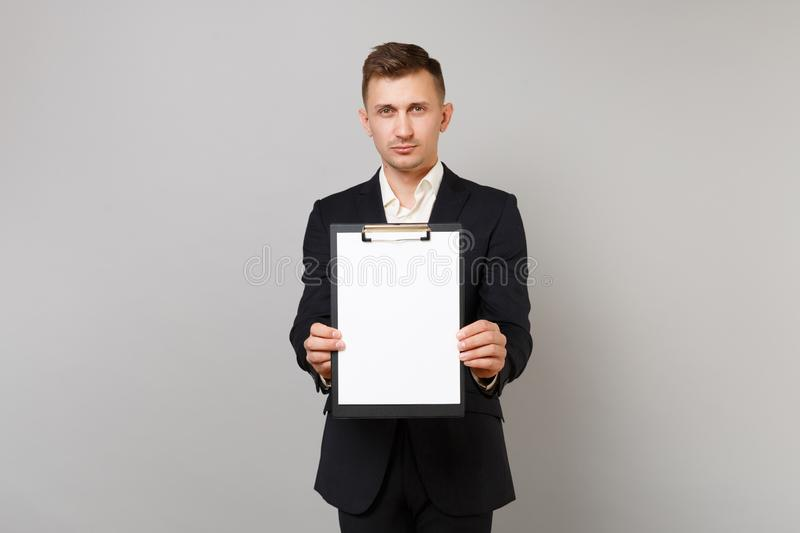 Serious young business man in classic black suit, shirt holding clipboard with blank empty sheet workspace isolated on stock image