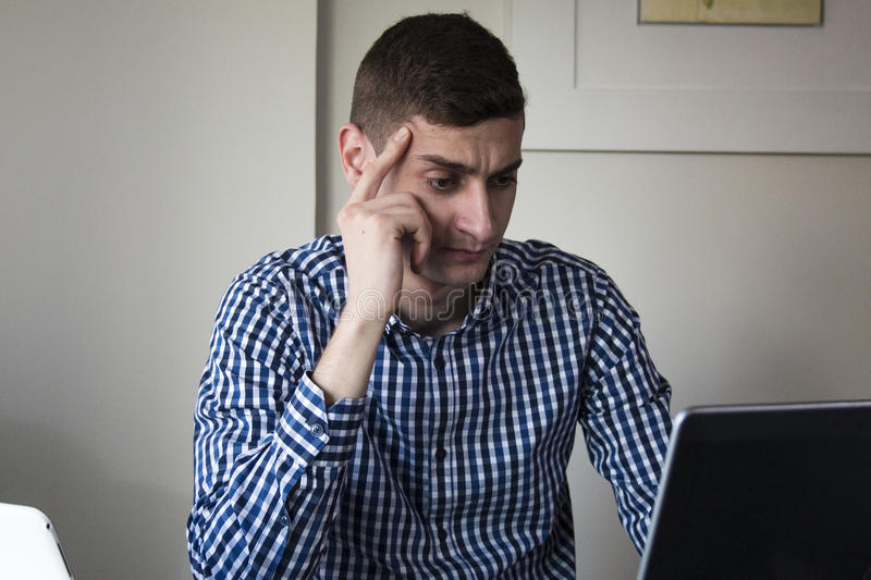 Serious young business man looking worried at laptop screen at home office. Desktop stock photo