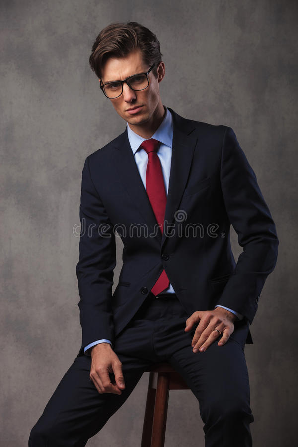 Serious young business man sitting on a stool royalty free stock images