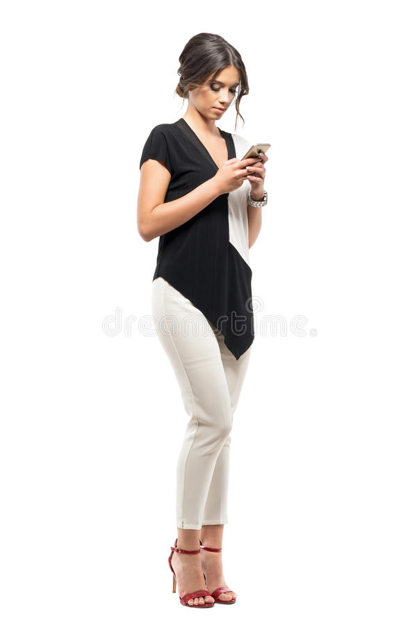 Serious young business woman in black and white suit reading message on the cellphone stock image