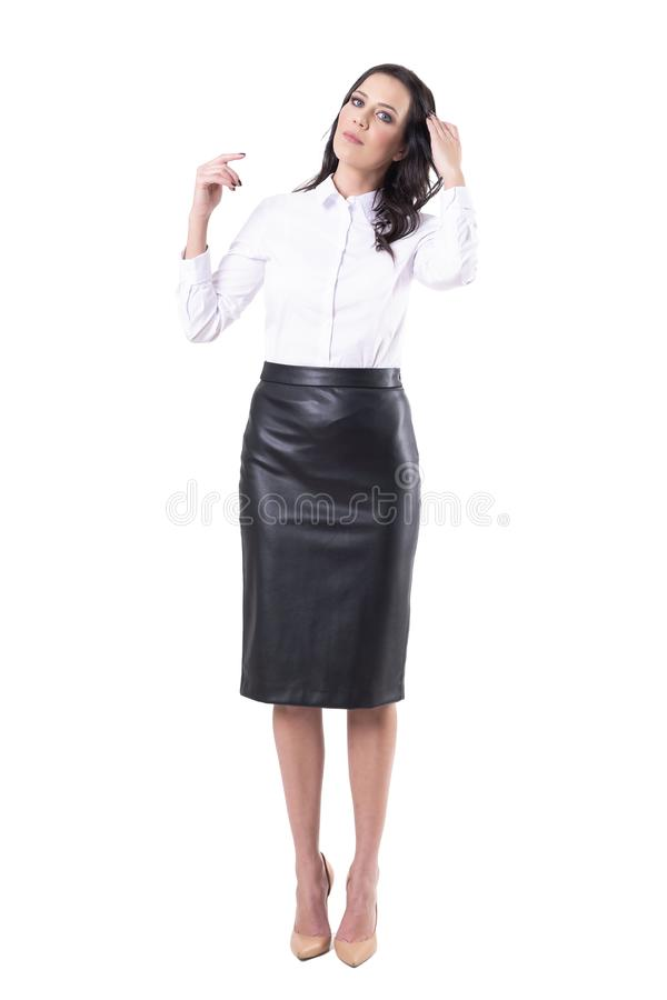 Serious young business woman in rush combing hair with hand getting ready for work or meeting royalty free stock photo