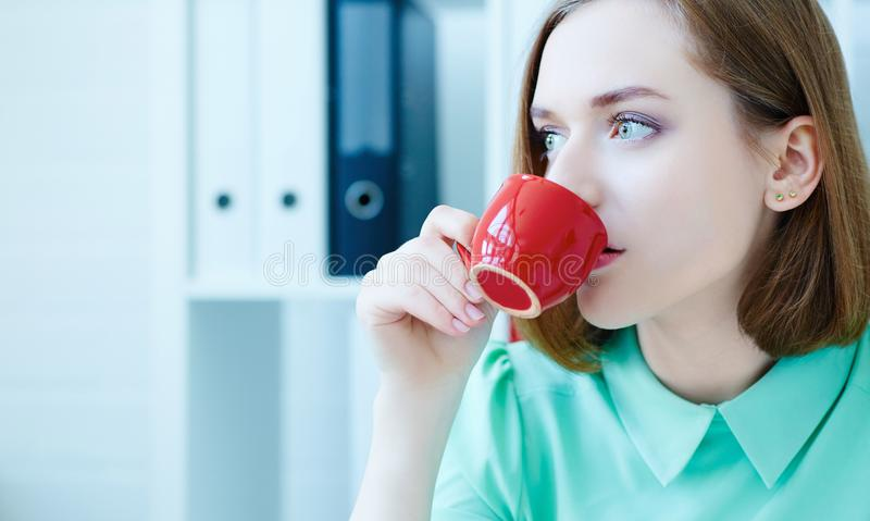 Young business woman thinking while drinking coffee. Beautiful young businesswoman being concentrated. royalty free stock photo