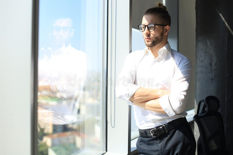 Serious young businessman keeping arms crossed and looking away while standing near the window stock photography
