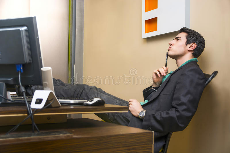 Serious young businessman sitting at desk in office thinking stock images