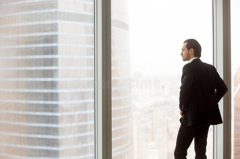 Serious young businessman standing in modern office, looking out. Concerned or serious businessman in expensive suit standing in office, looking outside the royalty free stock photos