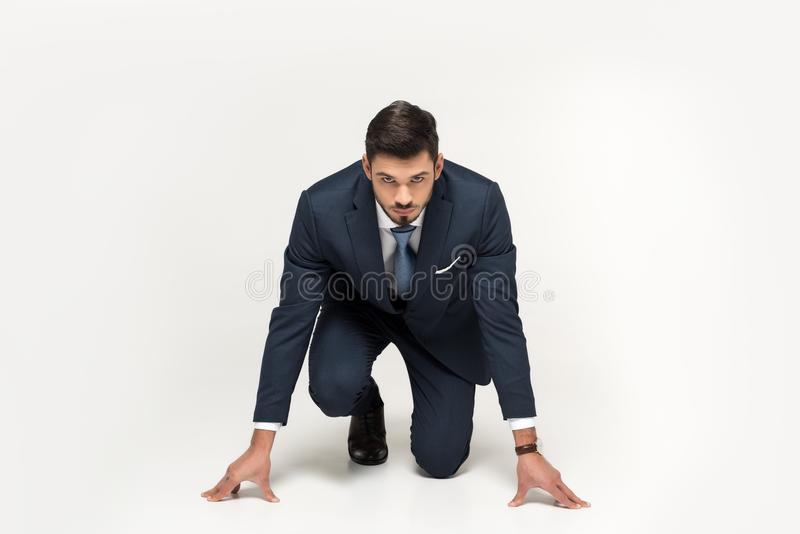 Serious young businessman in starting position ready to run. Isolated on grey stock image