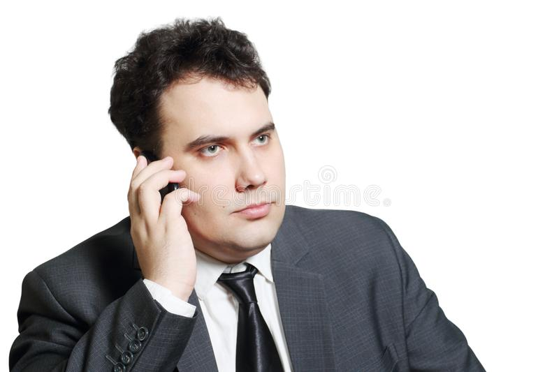 Serious young businessman in suit calls by mobile phone stock images