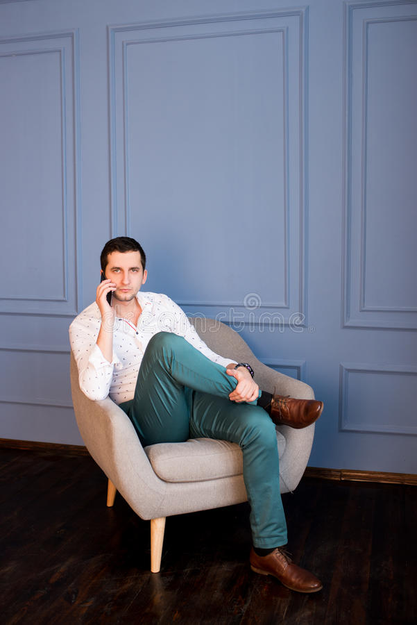 Serious young businessman talks cell phone sitting in armchair royalty free stock photography
