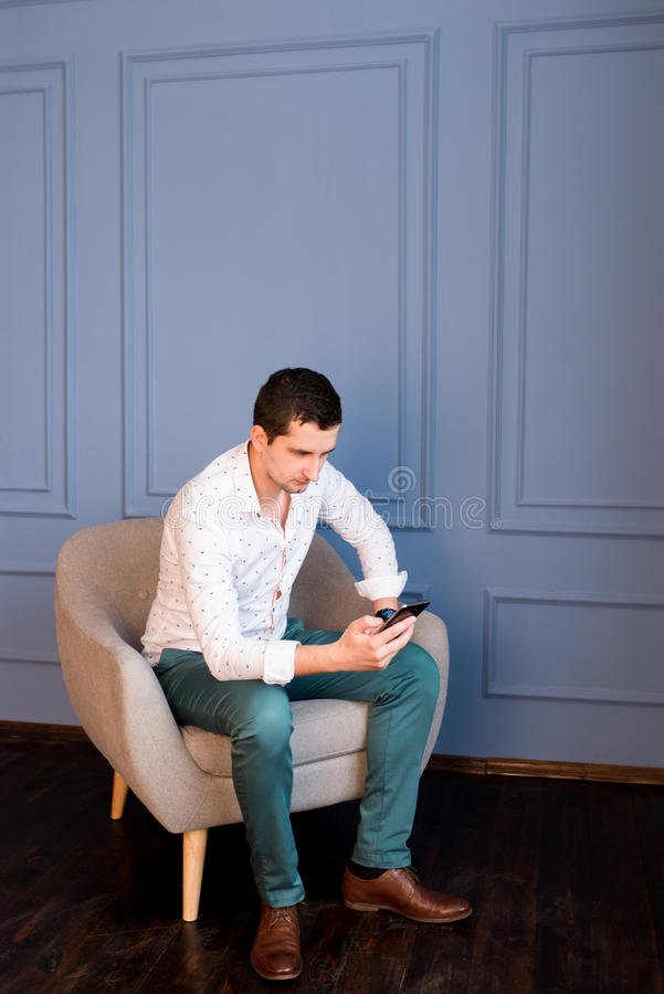 Serious young businessman writes a messages on his smartphone sitting in armchair stock image