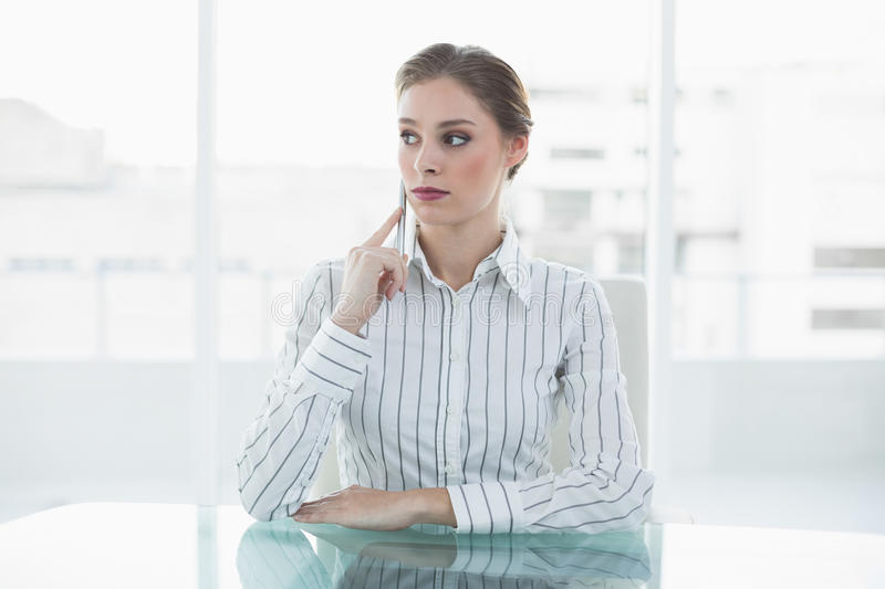Serious young businesswoman sitting at her desk royalty free stock images