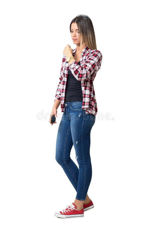 Serious young casual woman walking and adjusting shirt looking down. Full body length portrait isolated over white studio background royalty free stock photos
