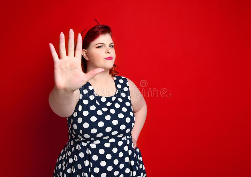 Serious young caucasian woman showing stop gesture with her hand. Serious young caucasian size woman plus showing stop gesture with her hand. She dressed in a royalty free stock photography
