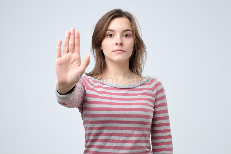 Serious young caucasian woman showing stop gesture with her hand. stock photos