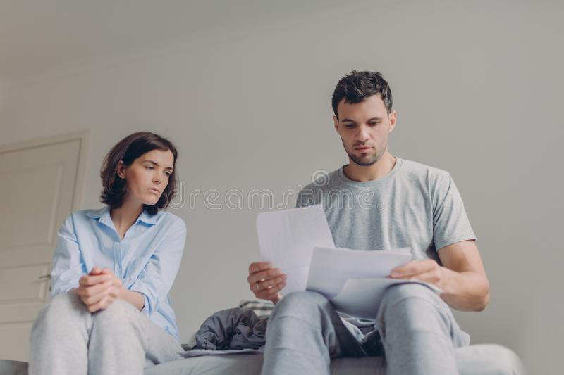 Serious young couple study documents together at bed, have serious looks, plan thier budget, pose against domestic interior,. Dressed in casual clothes. People royalty free stock images
