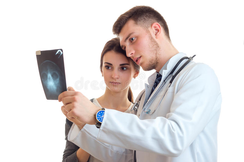 Serious young doctor in a white lab coat looking female x-ray royalty free stock photo