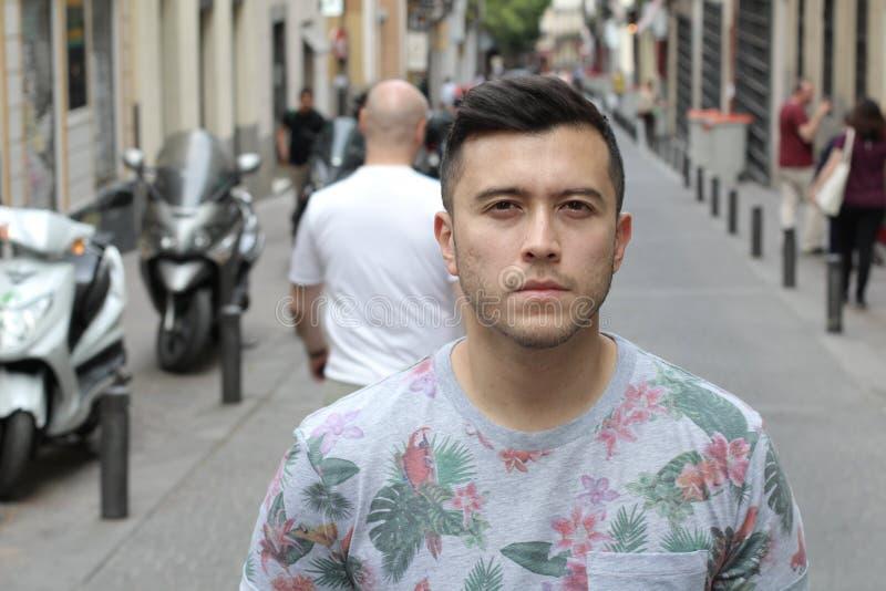 Serious young Eurasian man outdoors stock image