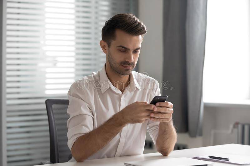 Serious young executive manager using internal company messenger application. royalty free stock photography