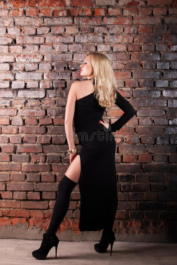 Serious young fashion woman. Young serious fashion woman in black dress over brick wall royalty free stock photo