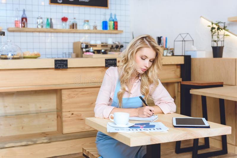 serious young female cafe owner taking notes while sitting royalty free stock photo