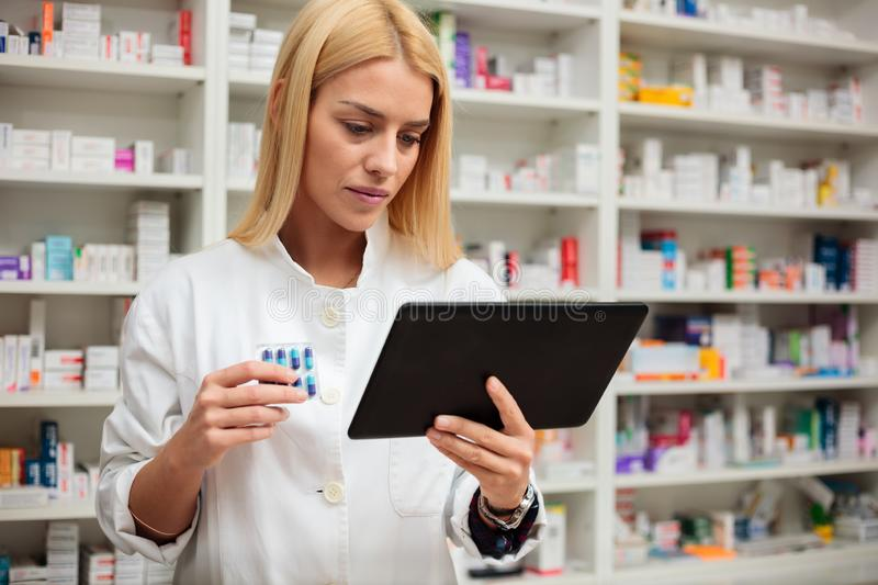 Serious young female pharmacist using a tablet in a drugstore stock image