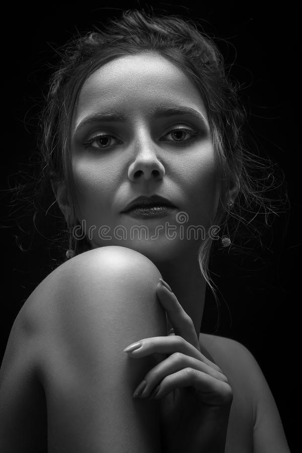 Serious young female. Serious sad young female portrait on black background, monochrome stock photography