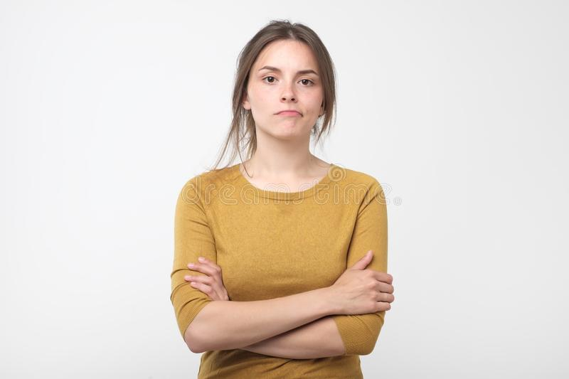 Girl looking at camera, her eyes full of distrust and disappoinmen. Serious young female wearing red pulover looking at camera, her eyes full of distrust and royalty free stock image
