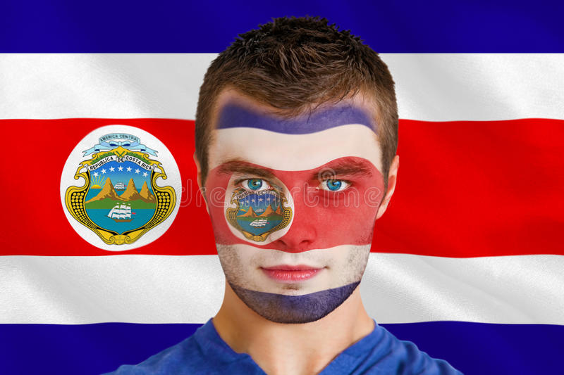 Serious young football fan in face paint royalty free stock image