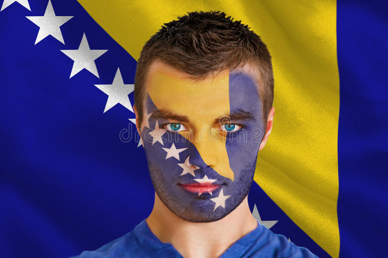 Serious young football fan in face paint royalty free stock images
