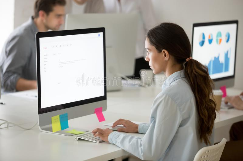 Serious girl intern focused on writing email working on computer. Serious young girl intern focused on writing email working on computer, young female office royalty free stock image