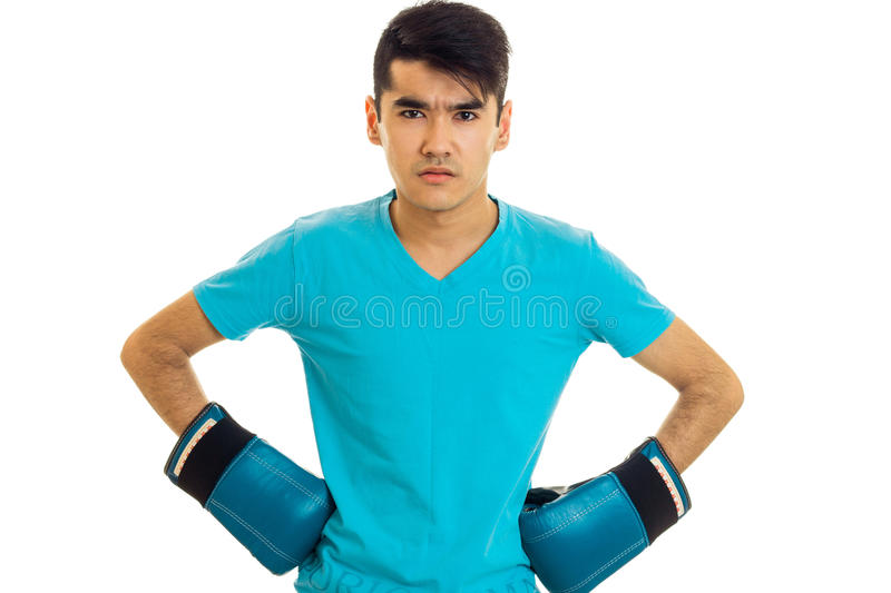 Serious young guy practicing boxing in blue gloves isolated on white background royalty free stock image