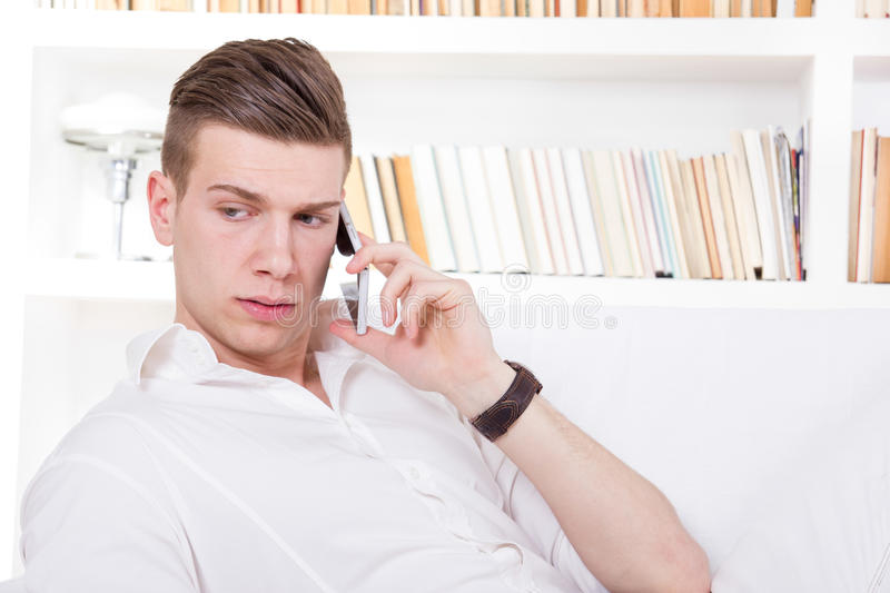Download Serious Young Guy In White Shirt Talking On The Cellphone Stock Photo - Image of handsome, home: 39500810