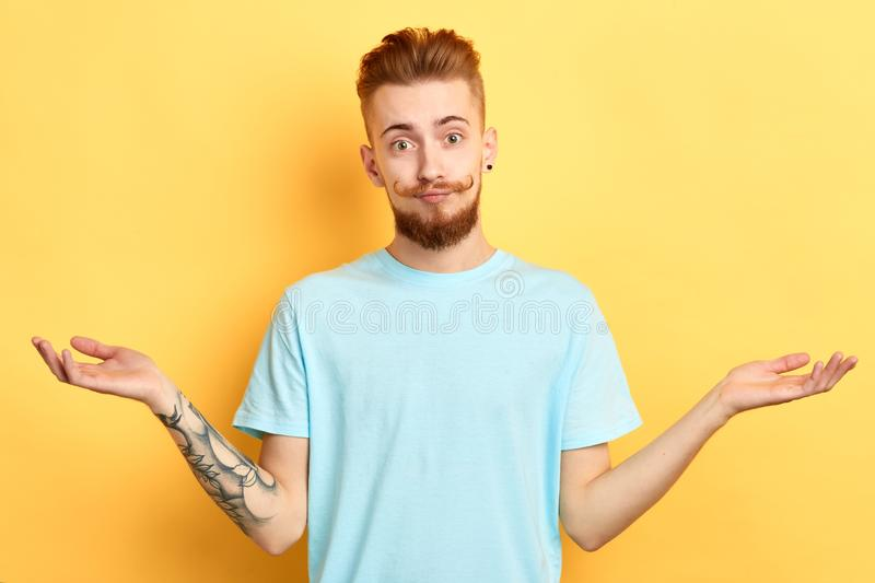 Serious young handsome man with raised hands posing to the camera stock image