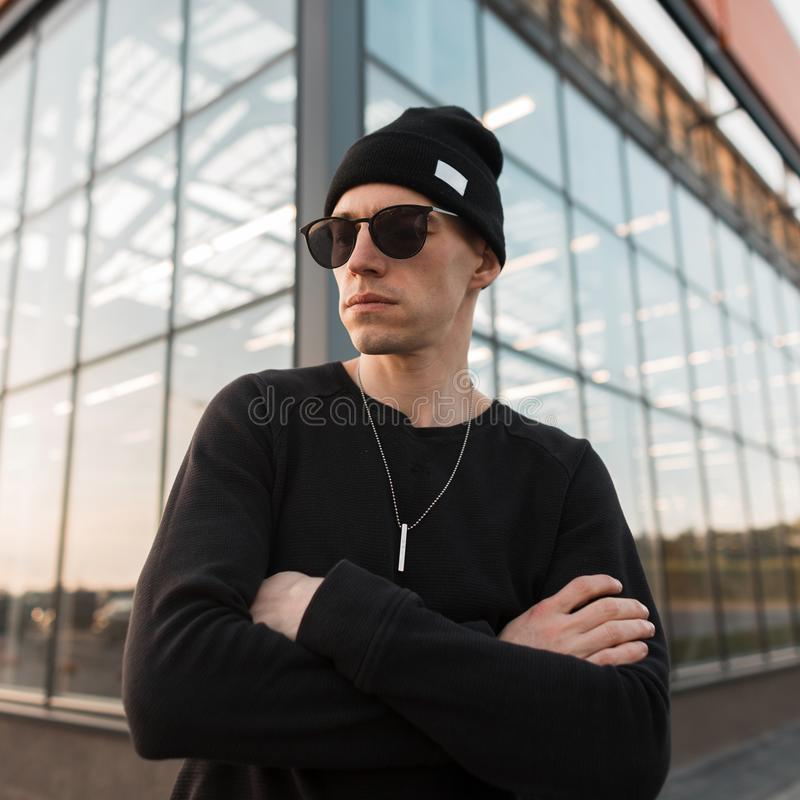 Serious young hipster man in black fashionable clothes in a knitted hat in trendy sunglasses is posing standing in a city. Near the glass building. Handsome guy stock photo