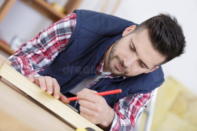 Serious young male carpenter working in workshop royalty free stock images