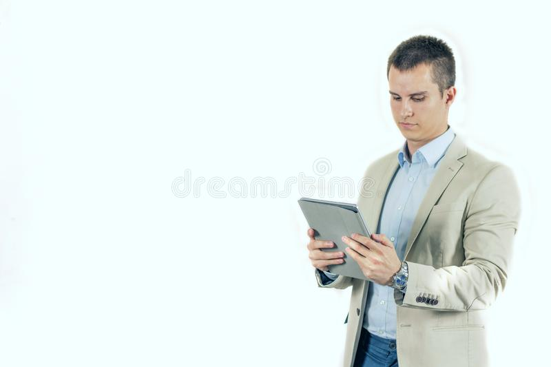 Serious young male using digital tablet checking news or information in tablet pc royalty free stock images