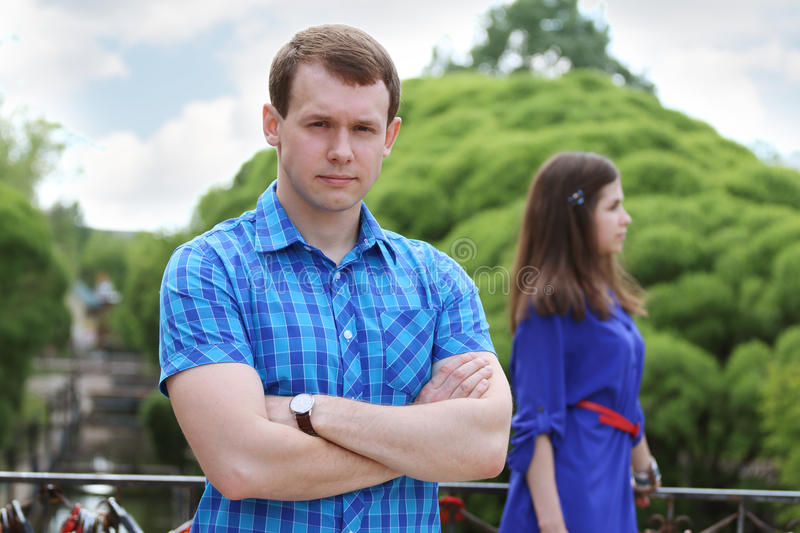 Serious young man in blue in summer park stock images