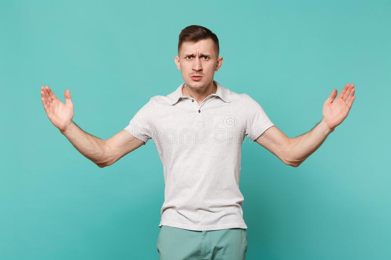 Serious young man in casual clothes gesturing demonstrating size with horizontal workspace isolated on blue turquoise. Wall background. People sincere emotions stock photo