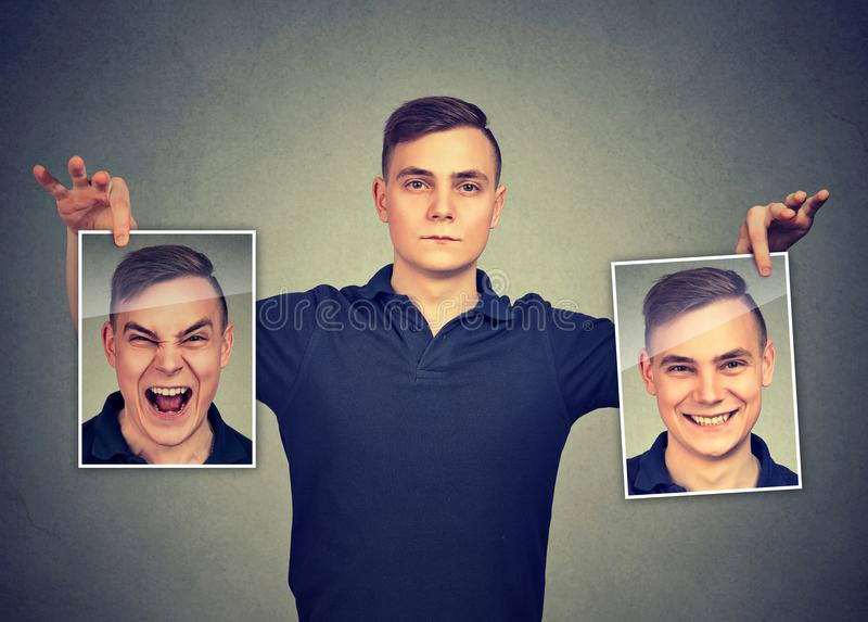 Serious man holding two different face emotion masks of himself stock image