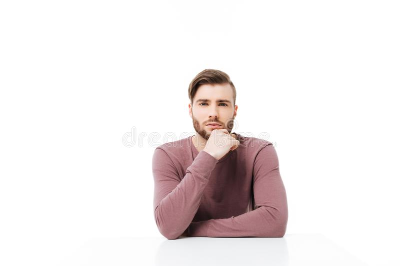 Serious young man looking at the camera sitting at the table isolated. Thinking pose with hand on the chin royalty free stock photography