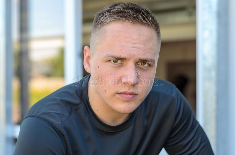 Serious young man looking intently at the camera. With a penetrating stare in a close up head and shoulders portrait royalty free stock image