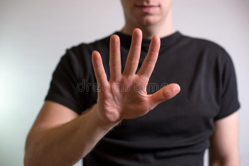 Serious young man showing stop gesture isolated on gray wall background royalty free stock photo