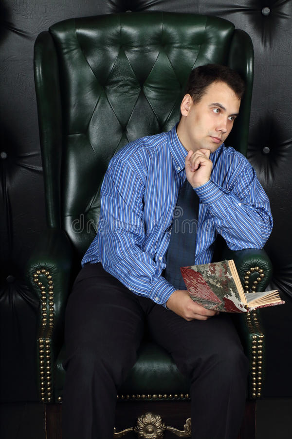 Serious young man sits with book in leather armchair stock images