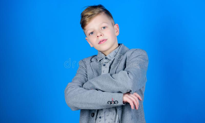 Serious young man. Small boy on blue background. Confident little boy. Cute boy child keeping arms crossed. Adorable stock image