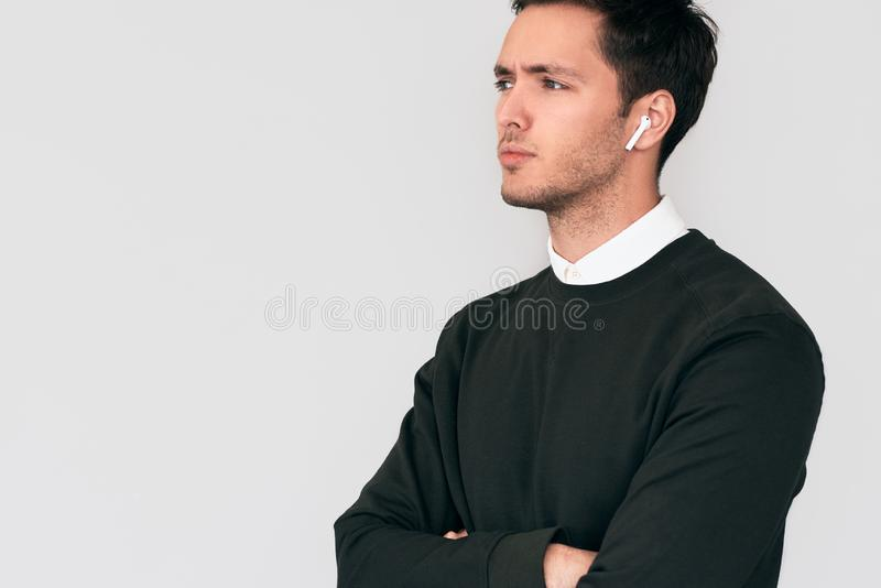 Serious young man standing with crossed hands and having a call via wireless earphones with a colleague isolated on white wall. stock image