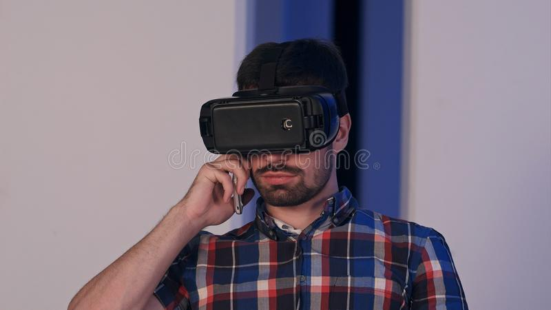 Serious young man in virtual reality glasses talking on the phone royalty free stock photos