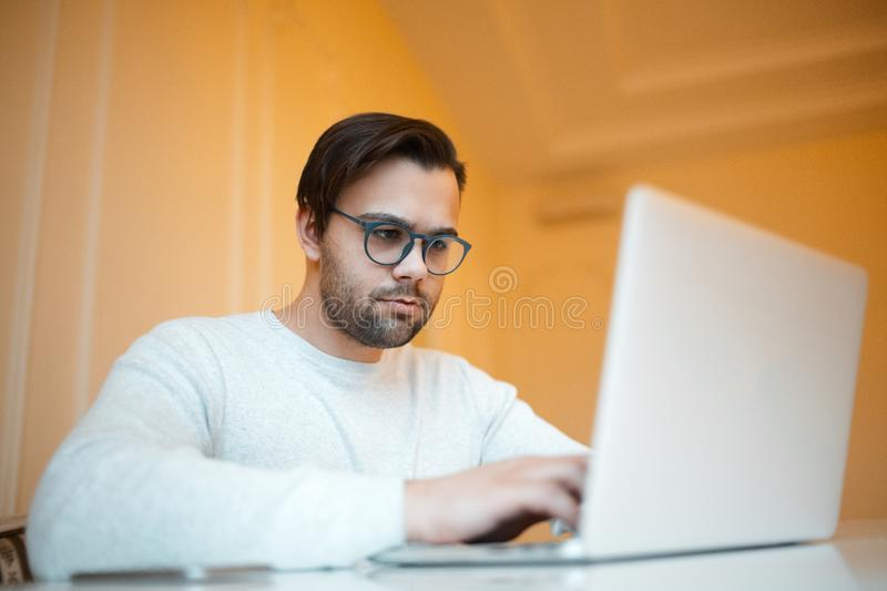 Serious young man working on laptop over yellow background. Dressed in white sweater and wearing blue glasses stock images
