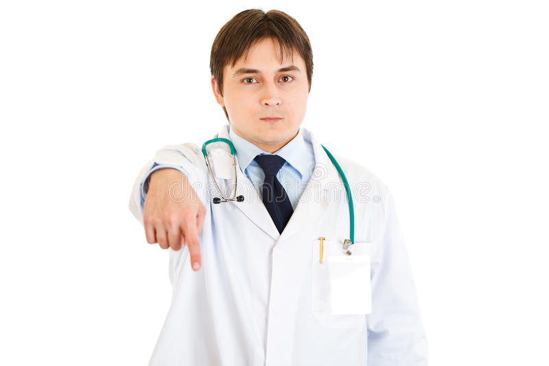 Serious young medical doctor pointing finger down royalty free stock images