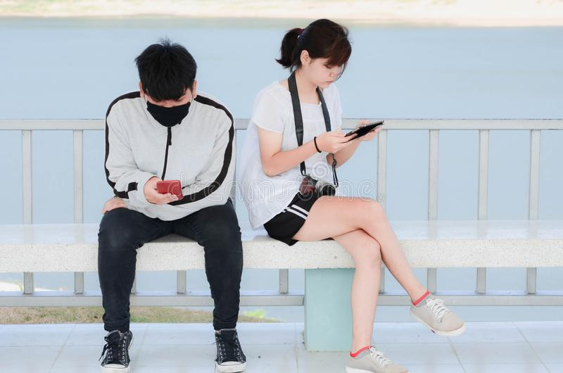 Serious young people using  smartphones sitting in park royalty free stock photography