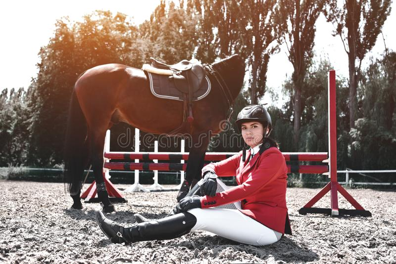 Serious young rider Girl and her horse posing after training. She loves the animals and joyfully spends her time in their. Young jockey Girl and her horse posing royalty free stock photography
