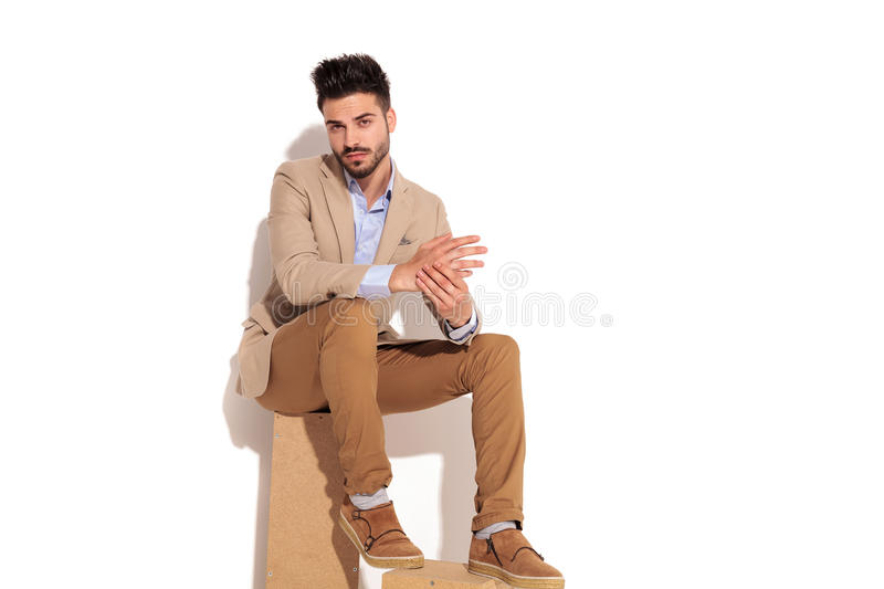 serious young smart casual man holding palms together while sitting royalty free stock photo